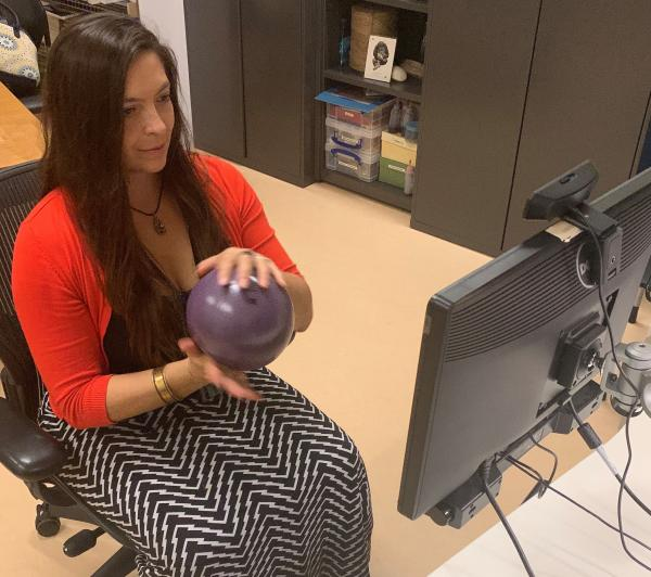 Woman sitting in chair with ball in front of computer screen
